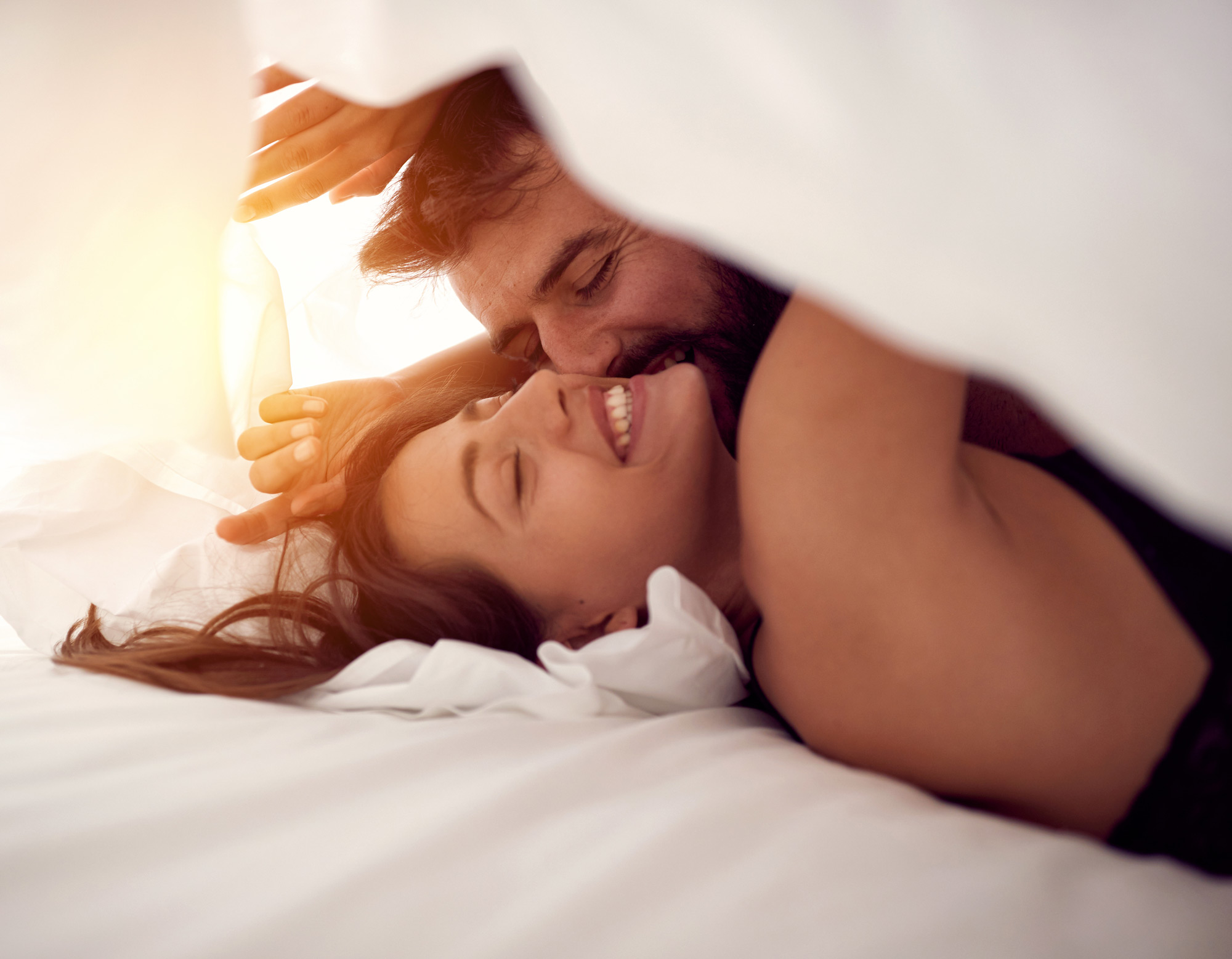 A man and woman romantically in bed