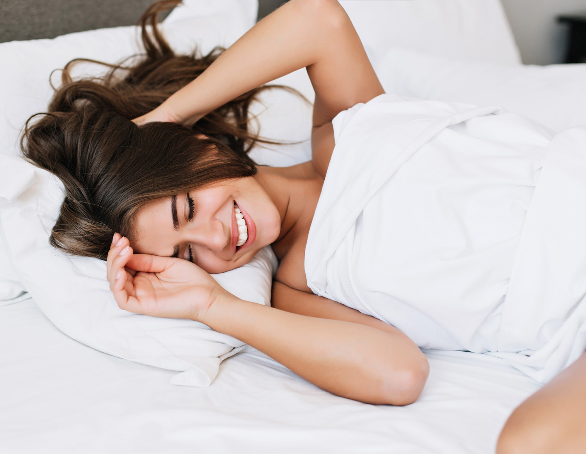 A woman confident and happy in bed
